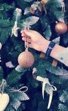 Boy& x27; la mano de s cuelga un juguete del Año Nuevo para el backgroun de la Navidad del Año Nuevo Imágenes de archivo libres de regalías