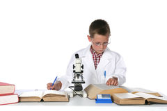 Boy in lab coat consulting text books Stock Photos