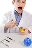 Boy in lab coat injecting blue liquid into apple. While laughing or yelling Stock Images