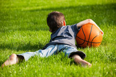Boy laid down on the grass. With orange ball Stock Photography