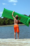 Boy at lake. A boy preparing to jump off a dock into lake with a raft Royalty Free Stock Photography