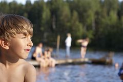 Boy at Lake. Boy looking out to lake with people on pier Stock Photography