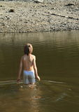 Boy in a lake. Boy in grey shorts standing in a lake and preparing for swimming Stock Photo