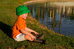 Boy By A Lake. A little boy with a fisherman's hat and cowboy boots sits by a lake in the late afternoon sun Stock Photo