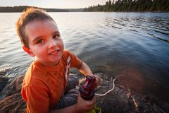 Boy by the lake. Boy pumping water from a lake Royalty Free Stock Images