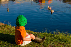 Boy By A Lake Watching Ducks. A small boy wearing cowboy boots and a fisherman's hat sits by a lake watching ducks who are also watching him Royalty Free Stock Photo