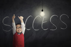 Boy with lamp and Success word. Portrait of a cheerful little boy showing thumbs up with bright lightbulb and Success word on the chalkboard, shot in the class Royalty Free Stock Images