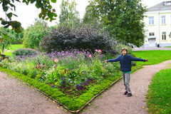 Boy in landscape with flowers trees and building Stock Photos