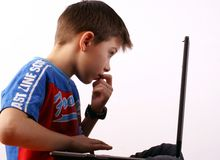 Boy and laptop. Eight years old boy working on a laptop royalty free stock photos