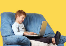 Boy with laptop Stock Images