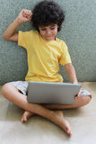 Boy with laptop. A boy sitting on the floor and enjoying his laptop Stock Photo