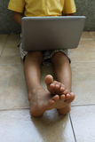 A boy with laptop. Sitting on the floor, no face Royalty Free Stock Images