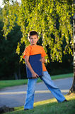The boy with the laptop. Costs near a tree Stock Photo
