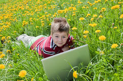 Boy with laptop computer lying on the grass Royalty Free Stock Photo