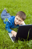 Boy with laptop computer on meadow. Stock Image