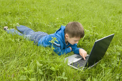 Boy with laptop computer on meadow. Stock Photo