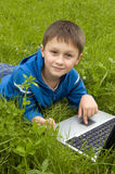Boy with laptop computer on meadow. Royalty Free Stock Photo