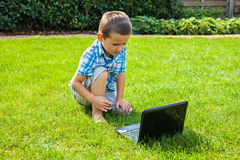 Boy with laptop computer outdoors Stock Photos