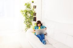 Boy with laptop on the couch Stock Photo