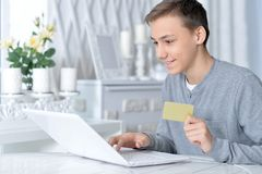 Boy with laptop and credit card. Teenage boy sitting at table with modern laptop and credit card, online shopping concept Royalty Free Stock Images