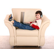Boy with laptop and headphone. Royalty Free Stock Images