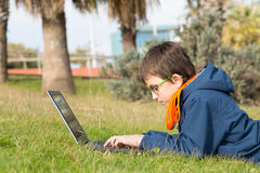 Boy with a laptop. Lying on the grass in a park Stock Image