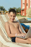 Boy with laptop near pool Royalty Free Stock Photography