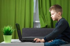 A boy at a laptop plays games, or watches a video. The concept of addiction to computer games, blurred vision, district mental stock photo
