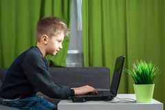 A boy at a laptop plays games, or watches a video. The concept of addiction to computer games, blurred vision, district mental royalty free stock images