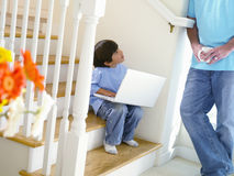 Boy (5-7) with laptop on stairs, looking at father Royalty Free Stock Image