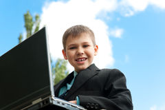 Boy with laptop studies outside Royalty Free Stock Image