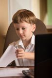 Boy with laptop at table Royalty Free Stock Photo