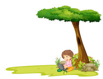 A boy with a laptop under a tree Royalty Free Stock Photo
