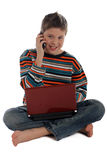 Boy with a laptop using the phone. Boy sitting using a laptop computer talking on the phone Royalty Free Stock Photo