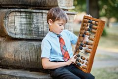 Boy with large abacus. Thoughtful schoolboy using a maths abacus calculation. Farewell Bell. day of knowledge. beginning of the stock photos