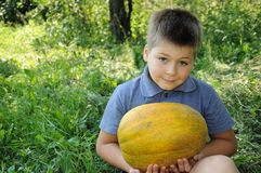 A boy with a large melon Royalty Free Stock Images