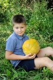 A boy with a large melon Royalty Free Stock Image