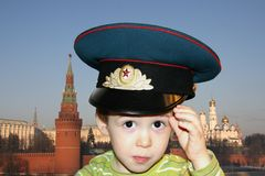 Boy with large Soviet cap. Charming small boy wearing  large Soviet military cap, hand raised to salute,  on a background of modern Moscow Royalty Free Stock Images