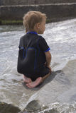Boy on a large wet stone Royalty Free Stock Photo