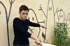Boy with laser sword. Teenage boy fighting with laser sword against  painted stick-men on a wall Stock Image