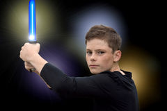 Boy with laser sword. Teenage boy fighting with lightsaber Royalty Free Stock Photos