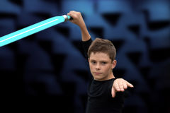 Boy with laser sword. Teenage boy fighting with laser sword. It looks like a dance royalty free stock photos