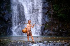 Boy laugh fishing at a waterfall countryside thailand.Fishing bo. Y asian by gaff in creek with beautiful background Stock Photos