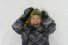 Boy laughing as snow falls on face Royalty Free Stock Photos