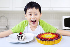 Boy laughing before eating birthday cakes at home Stock Images