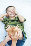 Boy laughing feet tickling. Hands tickling boy's feet Royalty Free Stock Image