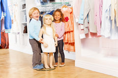 Boy and laughing girl stand with doll mannequin Royalty Free Stock Images