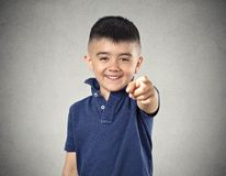 Boy laughing pointing finger at you. Laughter. Portrait boy laughing pointing finger at someone something, at camera gesture isolated grey wall background Royalty Free Stock Photo