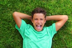 Boy laughing teenager laying green grass Royalty Free Stock Image