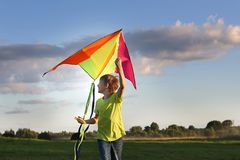 The boy launches a kite. Summer day. Sunny.The boy in a yellow t-shirt with a kite. A boy of European appearance on the field. stock image